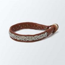 Authentique bracelet lapon fait main. En cuir de renne camel avec un tressage en fil d'argent et étain. Fermoir en corne de renne. Largeur 0,5 cm. Ce bracelet vieillira bien avec le temps.