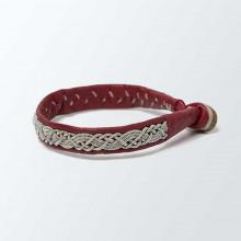 Authentique bracelet lapon fait main. En cuir de renne rouge avec un tressage en fil d'argent et étain. Fermoir en corne de renne. Largeur 0,5 cm. Ce bracelet vieillira bien avec le temps.
