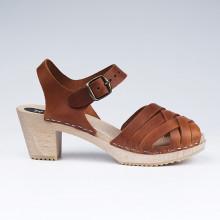 Authentiques sabot-sandales suédois avec un tressage en cuir cognac satiné. Hauteur du talon de 7 cm. Une gomme dure au niveau du socle en bois assure une protection et un confort supplémentaire. Prendre sa pointure habituelle.