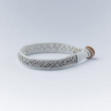 Authentique bracelet lapon fait main et façonné en Laponie.En cuir de renne blanc avec un tressage en fil d'argent et étain. Fermoir en corne de renne. Largeur 1 cm. Ce bracelet vieillit bien avec le temps, il se patine et devient de plus en plus joli. Existe en 2 tailles : Longueur du bracelet (sans le fermoir) 16 cm ou 17 cm, et rajouter 1cm avec le fermoir. Conseil : Le bracelet est d'autant plus joli lorsqu'il est porté ajusté. Par ailleurs le cuir va donner et se détendre.