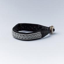 Authentique bracelet lapon fait main et façonné en Laponie. En cuir de renne noir avec un tressage en fil d'argent et étain. Fermoir en corne de renne. Largeur 2 cm. Ce bracelet vieillira bien avec le temps, se patine et devient de plus en plus joli. Existe en 2 tailles : Longueur du bracelet (sans le fermoir) 16 cm ou 17 cm, et rajouter 1cm avec le fermoir. Conseil : Le bracelet est d'autant plus joli lorsqu'il est porté ajusté. Par ailleurs le cuir va donner et se détendre.
