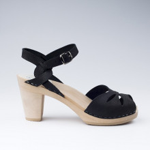 En exclusivité et en édition limitée. Très belles sandales suédoises de la marque Maguba en cuir suédé noir, au style élégant. Le bois est lisse et de couleur naturelle. La hauteur du talon est de 9 cm avec un plateau de 2 cm. La lanière est perforée sur le dessus avec de jolis motifs. Les lanières autour de la cheville sont entrelacées. Une gomme dure au niveau du socle en bois assure une protection et un confort supplémentaire. Prendre sa pointure habituelle.
