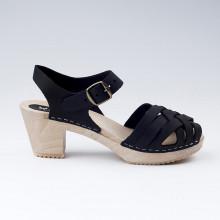 Authentiques sabot-sandales suédois avec un tressage en cuir gras noir. Hauteur du talon de 7 cm. Une gomme dure au niveau du socle en bois assure une protection et un confort supplémentaire. Prendre sa pointure habituelle.