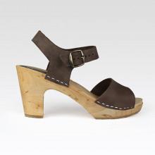 Authentiques sabot-sandales suédois en cuir nubuck marron foncé avec 1 lanière unique variant entre 3,5 et 6 cm de largeur. La hauteur du talon est de 9 cm. Une gomme dure au niveau du socle en bois assure une protection et un confort supplémentaire. Prendre sa pointure habituelle.